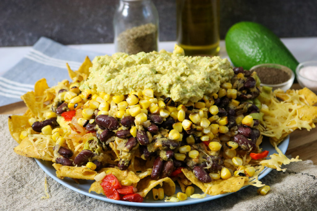 Top with onion mixture, corn, beans, and avocado sauce