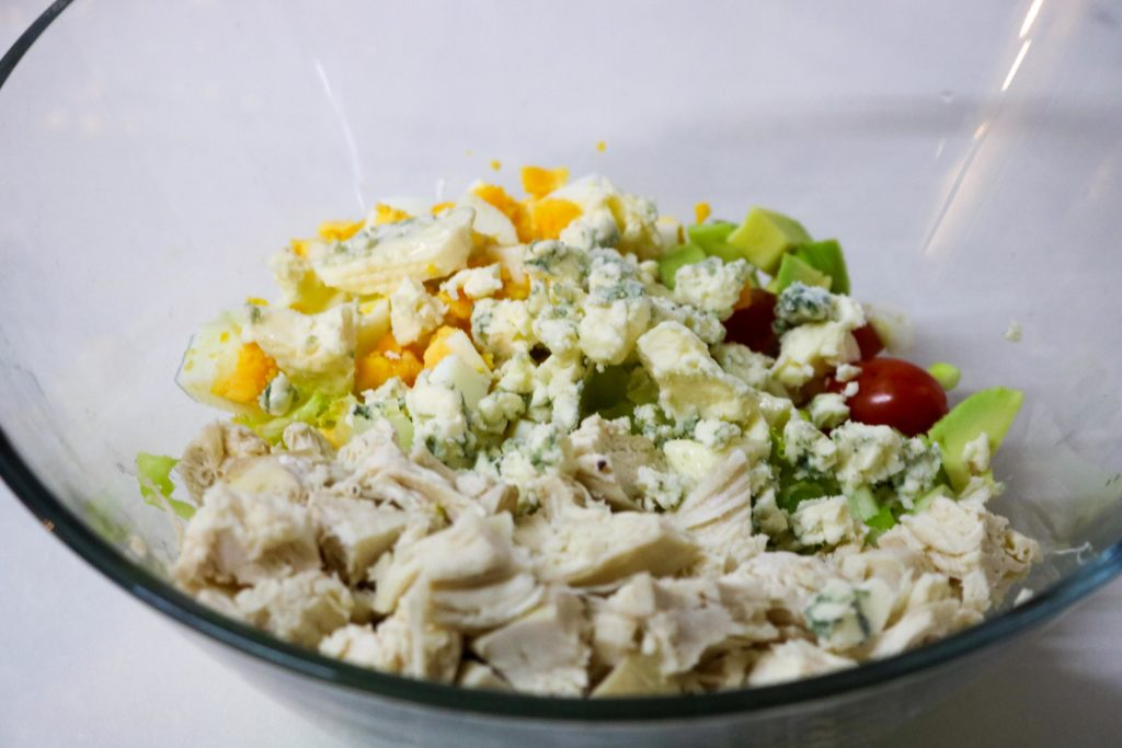 Add turkey, egg, bacon, blue cheese, tomatoes, avocado and green onion
